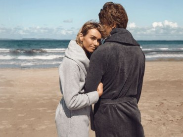 Couple with contrasting Karmameju bathrobes on a beach with the sea in the background